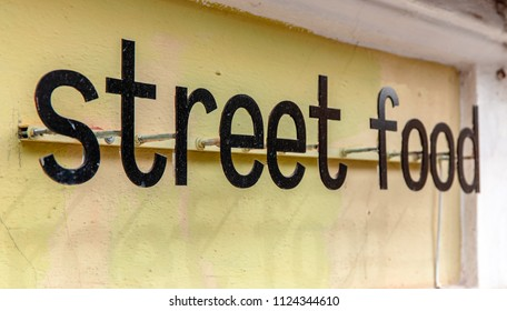 Street food sign on yellow old wall. Low shallow focus
