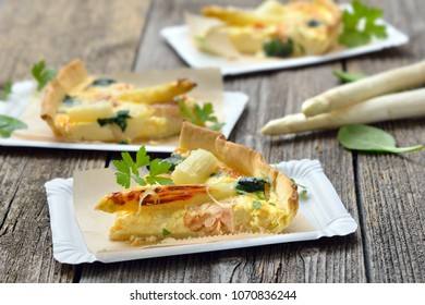 Street food: Slices of fresh quiche with white asparagus, smoked salmon and spinach on paper plates