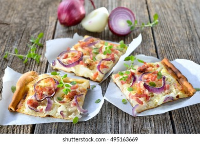 Street food: Slices of hot baked tarte flambee from Alsace with onions, bacon and sour cream served on parchment paper