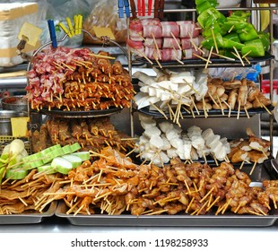 A street food stall in Taiwan offers a variety of meat and vegetable skewers