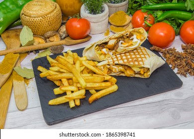 Street food, tacos with french fries, served on a wooden table, presented with slate and food decoration in the background
