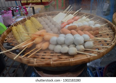 Street food in Thailand concept, meatball, fishball, Tofu and wonton with bamboo sticks on a bamboo tray covered with hot cooking smoke for taking away, eating and walking along food street