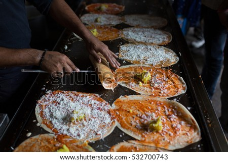 A street food vendor prepares Paneer Butter Masala Dosa in Hyderabad,India