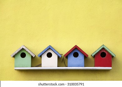 Street of four colorful birdhouses hanging on a yellow wall