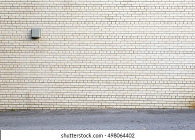 street in front of white brick wall