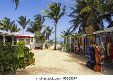 A street full of street vendors leading to a beach on a Caribbean Island