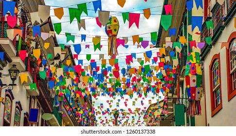 Street fuly decorated with multicolored paper flags and balloons during june party in Brazil. Location: Ouro Preto, world famous human historic patrimony city