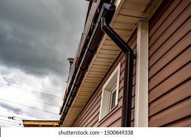 Street gutter system mounted under the roof of the house and on the wall