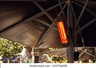 The street heater hangs switched on under the tent on the street
