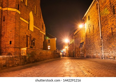 A street with historic brick buildings during a night in Grudziadz in Poland