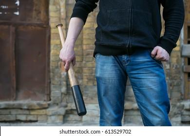 Street hooligan is holding a baseball bat.
