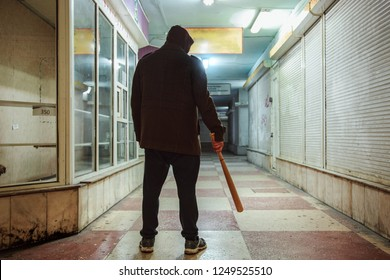 Street hooligan with wooden bat in subway.