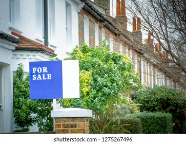 A street of of house with 'For Sale' sign- UK
