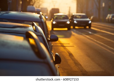 Street inside city, morning twilight with parking cars, two further blurred with illuminated headlights on the road, one pass the other (copy space)/Car Overtake Street Scene