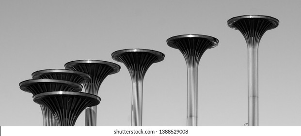 Street installations with seven metal funnel pillars in black and white.