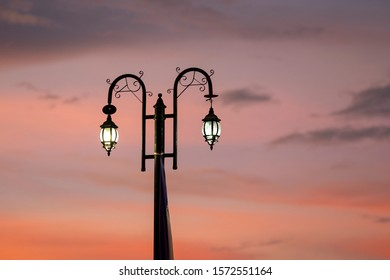 Street iron lantern on a post with beautiful red, orange and pink sunset sky in the background. Selective focus, space for copy.