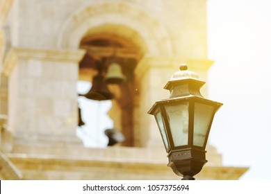 Street lamp with bell tower in the background and sun backlight