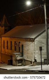 Street lamp lighting up exterior of old wooden building in a small Midwest town on a Winter's night.