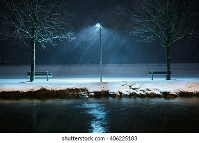 A street lamp in a local park illuminates the falling snow.