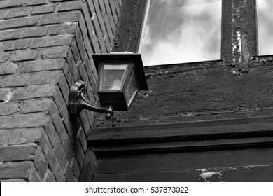 Street lamp on the brick wall of the house (black-and-white photograph)