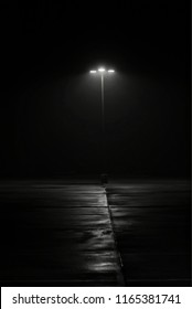 Street lamp on foggy night. Film noir feel with a sense of mystery and intrigue and shadowy textures on the ground. Minimalist image with copy space.