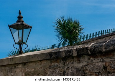 Street lamp on stone wall in foreground against a blue sky and palm tree peeking over top of fence
