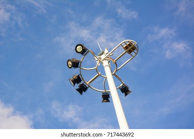 Street lamp post with multiple spot lights.  Blue sky with clouds.