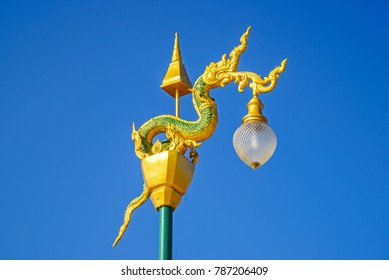 Street lamp post with serpent or Naga statue at above in thailand.