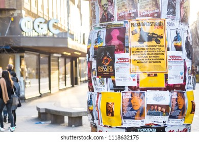 Street lamp post in the walking street in front of CGC clothing store covered by colorful advertising flier posters for public advertising show, concert, and product on Karlstad, Sweden. 13 April 2018