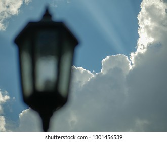 Street lampion in the style of the lantern, on a sunny day, sunny light on white clouds