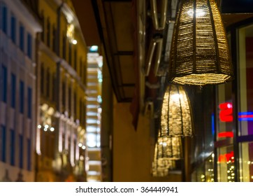 Street lamps near the restaurant slowly swaying in the wind at night