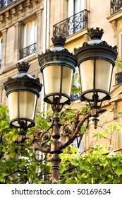 Street lamps with ornate ironwork in downtown Paris.  Traditional apartments with balconies are seen in the background.
