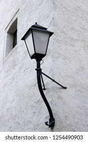 Street lantern with glass lampshade and cast iron bracket on wall of old building. Astract photo of medieval architecture fragment.