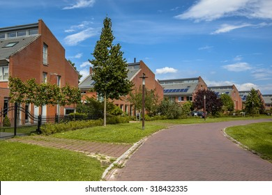 Street with large freestanding detached family houses in a suburb of Wageningen City, Netherlands