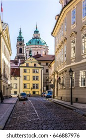 """A street in the """"Lesser town"""" district. Church of Saint Nicholas . Area of the Old City. Prague, Czech Republic."""