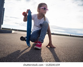 Street life style: A girl in pink sunglasses and pink sneakers sits on the asphalt and holds a blue skateboard. Portrtet in the style of the deadpan.