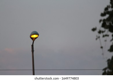 A street light dimly glowing yellow in the evening by the main road in india. A pole is holding a faintly illuminated light up