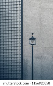 A street light in front of a grey wall in London.