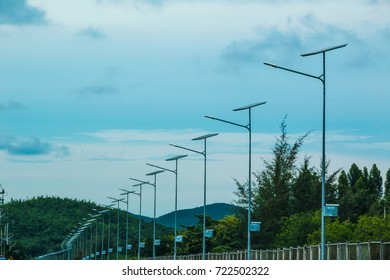 Street light pole with solar cell panel with mountain and blue sky background.