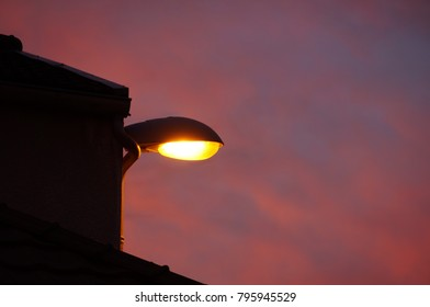 Street light with red sky on background. Lite Lamppost.