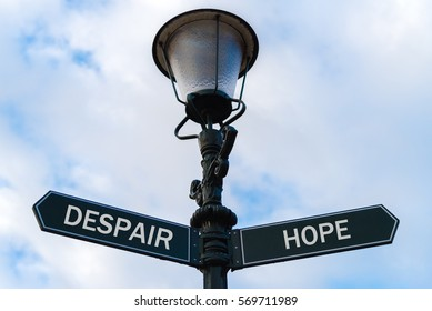 Street lighting pole with two opposite directional arrows over blue cloudy background. Despair versus Hope concept.