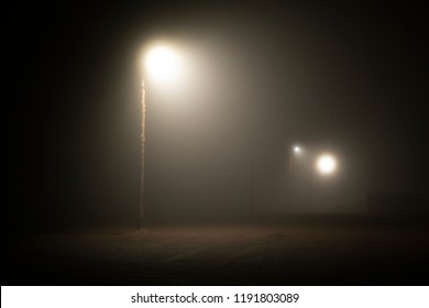 Street lights foggy misty night lamp post lanterns deserted road. Lonely street at night in the light of lanterns. foggy night parking lot