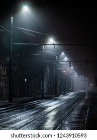 Street lights foggy misty night. Tram route on a city street.