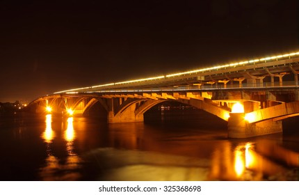 Street lights on the bridge over river reflected in water at night