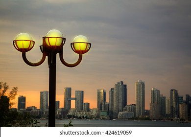 Street lights on Toronto Island with skyscrapers across Lake Ontario in the background at sunset.