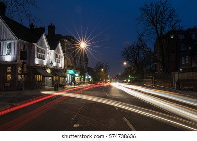 A street in London at night with a pub on the left and the trace of the headlamps from the cars