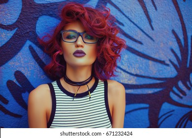 Street look of Fashion and Sexy woman with red curly hairstyle posing near graffiti wall