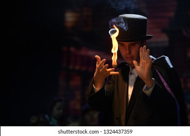 A street magician manipulates a ball of flame for an illusion during a stage performance
