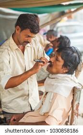 Street man barber shaves a customer. India, Govardhan, November 2016