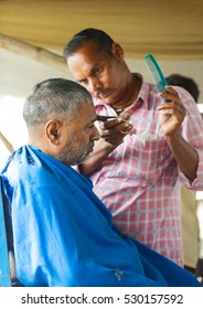 Street man barber shaves a customer. India, Govardan, November 2016